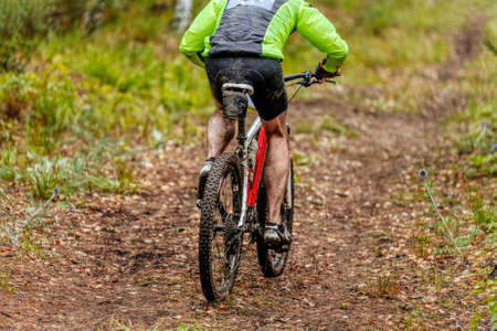 dirty man cyclist riding mountain bike in forest trail Banque d'images