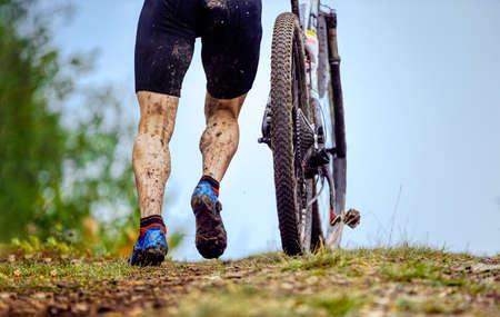 dirty feet male cyclist and mountain bike walking uphill