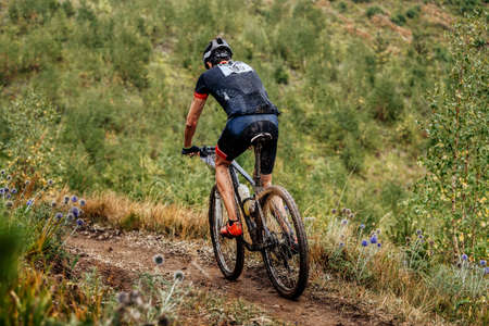 dirty cyclist athlete biking mountain bike on trail. cross country cycling competition