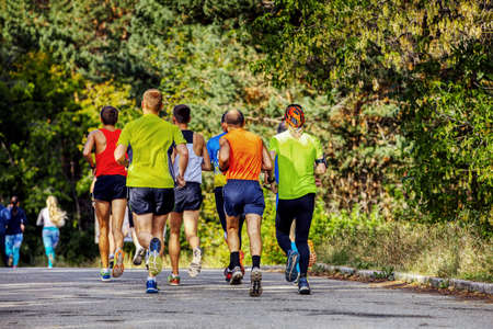 A group of male runners running marathon race in autumn park