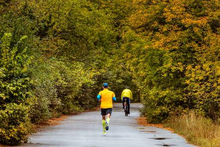 A athlete runner run marathon in autumn park