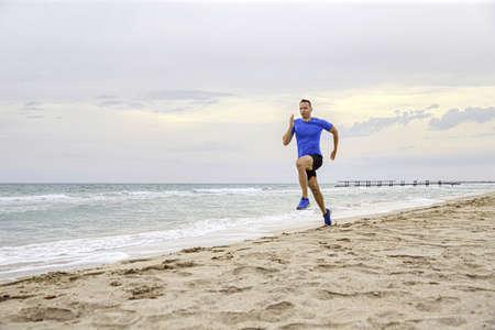 male runner running an evening training on sandy sea beach
