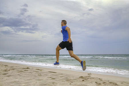 man runner in blue shirt and black shorts running on sandy beach