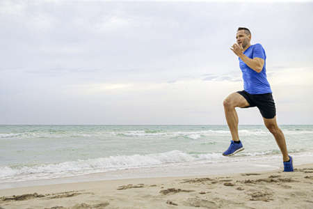 middle-aged man runner run on sandy beach of sea Banque d'images