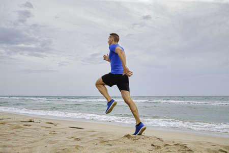 back man athlete runner running on sea sandy beach