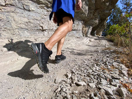 Sochi, Russia - October 6, 2020: legs man in running shoes Salomon Speedcross 4 gtx hiking on mountain trail