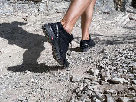Sochi, Russia - October 6, 2020: legs man in running shoes Salomon Speedcross 4 gtx hiking on mountain trail