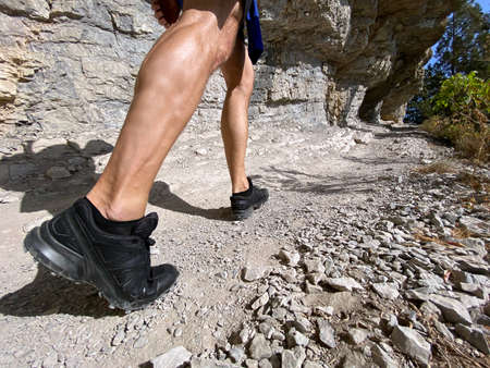 man in running shoes hiking on mountain trail in summer Banque d'images