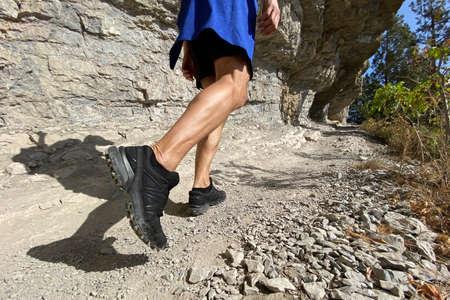legs man in trekking shoes walking on mountain trail