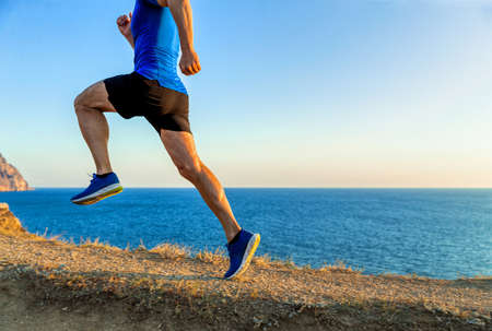 man athlete runner running uphill in background of sea and sky