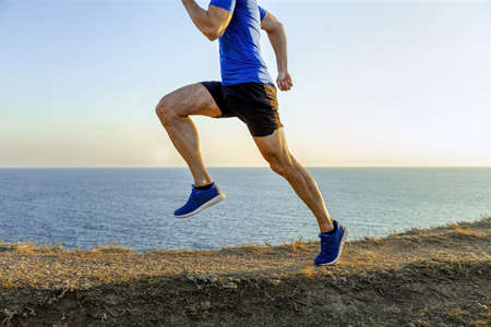 man athlete runner running mountain trail in background of sea and sky Banque d'images