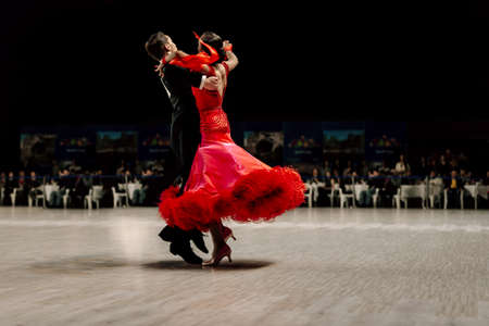 dancers couple man in black tailcoat and woman in red ball gown