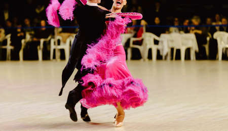 dancers man in black tailcoat and woman in pink ball gown at dance competition