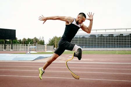 disabled male runner on prosthetic leg on track of stadium