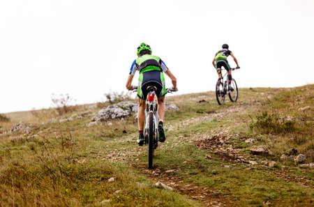 two athletes mountain bikers riding mountain trail race