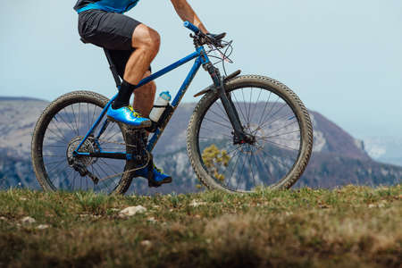 closeup man on mountain bike riding trail in background of mountain