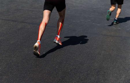 legs two male runners run marathon on dark asphalt Zdjęcie Seryjne