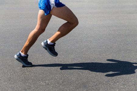 legs male runner athlete run on gray asphalt Zdjęcie Seryjne