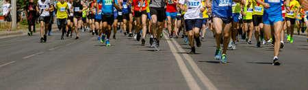 large group of leg runners athletes run urban marathon