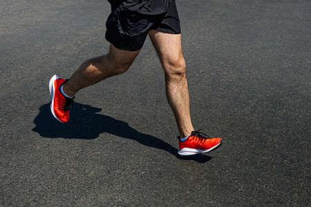 legs runner man in bright orange shoes run on dark asphalt
