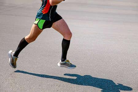legs male runner in black compression socks run road