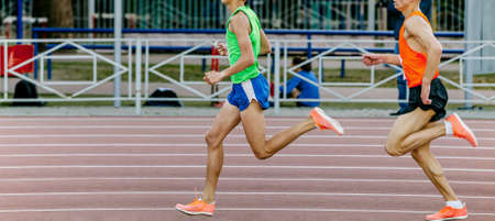two male athletes runners run at stadium track and field competition