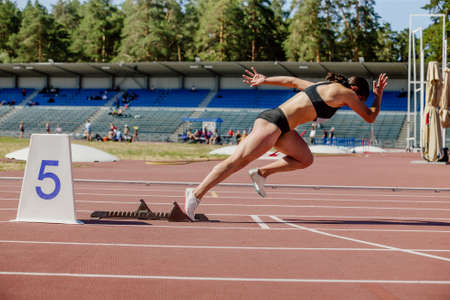 young female sprinter running from starting blocks to competition