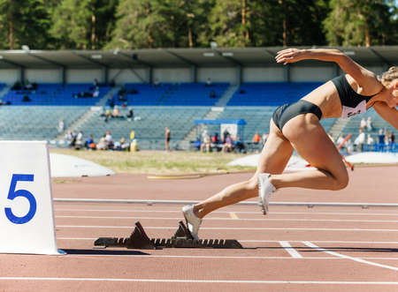 girl runner sprinter running from starting blocks to competition