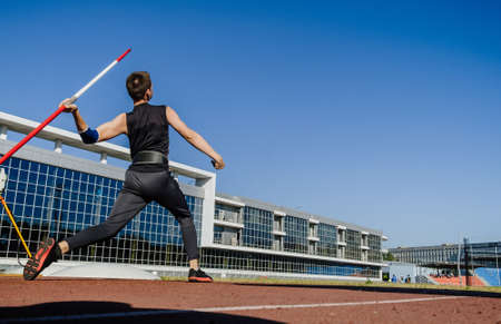male athlete javelin throw at track and field competition