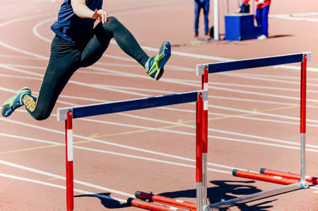 girl athlete run hurdles track and field race