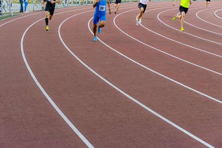 group male athletes run track sprint race