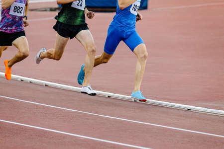 group male runners run middle distance race at stadium