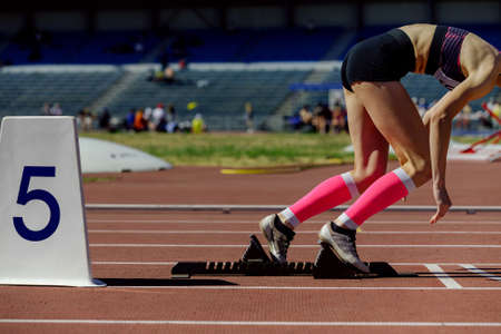 girl athlete in compression socks running from starting blocks