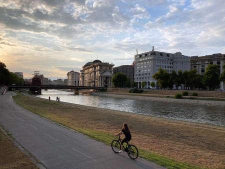 girl on bike riding in embankment during sunset