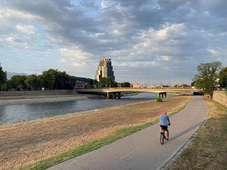 man on bicycle riding river embankment during sunset
