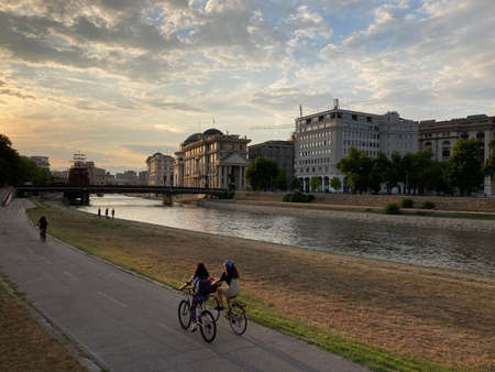 two girls on bicycles riding embankment during sunset
