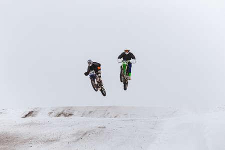 two motorcycle racers jump snow covered hill race enudro Zdjęcie Seryjne