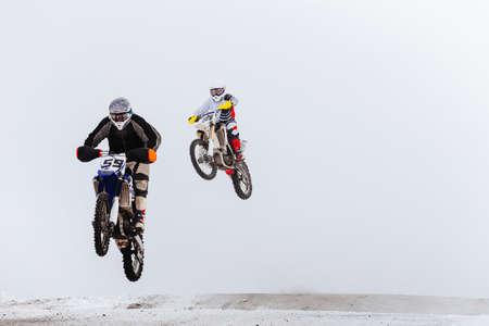 two motorcycle racers jump winter enduro race