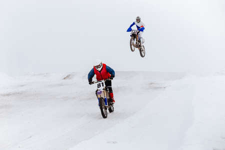 two motorcyclists riding winter enduro race on snow