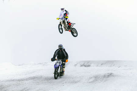two motorcycle racers riding on snowy trail race