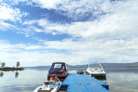 Miass, Russia - June 7, 2016: boats near pier on lake in background blue sky and mountains