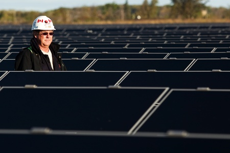 Sarnia Ontario Canada. October 2010. Steve Nagy of First Solar walks between the rows of photovoltaic collectors at the Sarnia Photovoltaic (PV) Farm. When opened in 2010 it was the worlds largest solar farm.