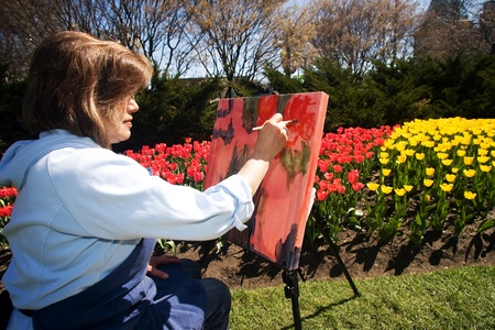 Ottawa Ontario Canada. May 2011. Artist Lina Yachnin paints at the National Tulip Festival. The festival began when the Dutch Royal family donated 100,000 tulip bulbs to Canada in appreciation of providing a safe house to its family during World War 2.