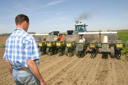 southwestern ontario: Parkhill, Ontario - May 3, 2006. A Canadian farmer watches as another farmer drives a tractor towing a planting machine. Loaded in the planter is corn seed that is being planted to a percise depth in the soil.