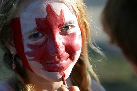 festividades: London, Canad� - 01 de julio de 2007: Una joven tiene la una hoja de arce roja pintada en su cara durante las fiestas de d�a de Canad�.