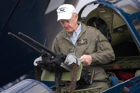 maching: St. Thomas, Canada - June 24, 2011: Ted Short cleans his M1919 Browning maching gun in a Curtis SB2C Helldiver, World War II dive bomber parkded on the tarmac at the Great Lakes International Air Show.