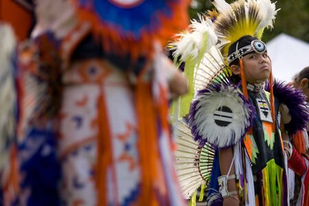 London, Canada - September 17, 2011: A First Nations Canadian wearing traditional clothing participates in a Pow Wow dance during the annual Native Harvest Festival and Pow Wow at the Attawandaron Village located in the Museum of Ontario Archaeology in Lo Editorial