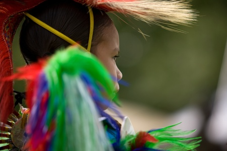 first nations: London, Canada - September 17, 2011: A First Nations Canadian wearing traditional clothing participates in a Pow Wow dance during the annual Native Harvest Festival and Pow Wow at the Attawandaron Village located in the Museum of Ontario Archaeology in Lo