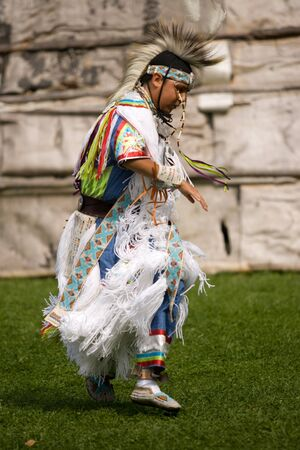 pow: London, Canada - September 17, 2011: A First Nations Canadian wearing traditional clothing participates in a Pow Wow dance during the annual Native Harvest Festival and Pow Wow at the Attawandaron Village located in the Museum of Ontario Archaeology in Lo