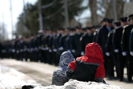 converged: March 24, 2011. Listowel, Ontario.  Two young children watch the procession of Firefigthers walk past them. Thousands of firefighters from Ontario, Quebec and the United States converged on Listowel to honour volunteer firefighters Ken Rae 56 and Raymond